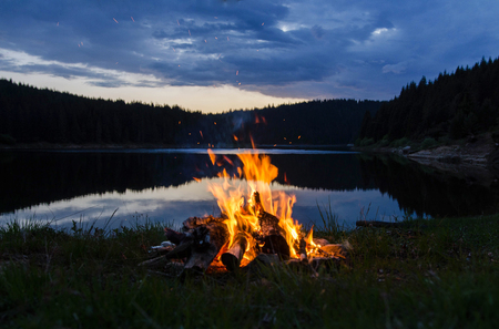 Campfire after sunset in the mountains next to a lake