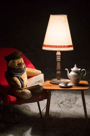 Teddy bear read a book outside in a winter night - surreal scene 스톡 콘텐츠