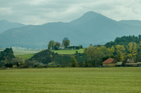 Ladnscape from Slovakia - green meadows and fields in the background the mountains- industiral buildings and houses