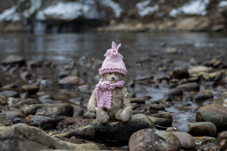 Teddy bear in warm clothes sits in the riverside