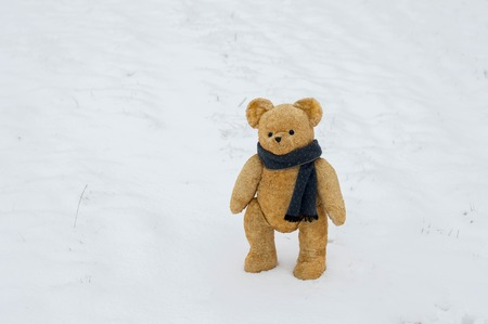 Teddy bear walks in the snowy field - European winter scene with an old toy