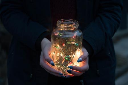 Girl holds christmas lights in glass jar