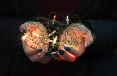Girl holds christmas lights in her hand