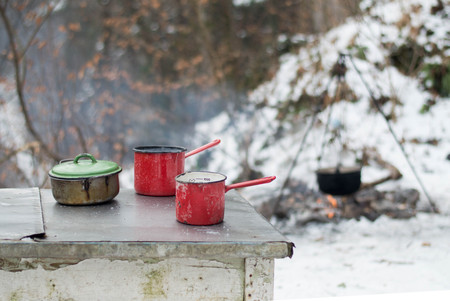 Enamel dishes on the table - cooking outdoors in the winter by campfire 版權商用圖片
