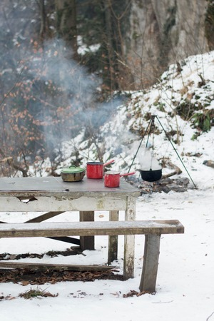 Enamel dishes on the table - cooking outdoors in the winter by campfire Banque d'images