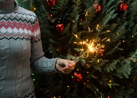 Christmas scene - woman in knitted winter sweater holding sparklers before the decorated christmas tree Banque d'images