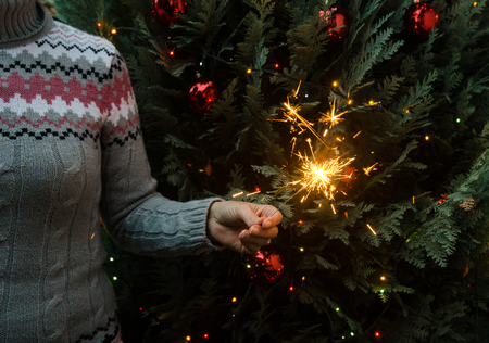 Christmas scene - woman in knitted winter sweater holding sparklers before the decorated christmas tree 版權商用圖片