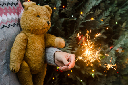 Christmas scene - woman in knitted sweater holding an old teddy bear and sparkler before christmas tree