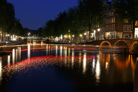 excursions: Amsterdam,  Netherlands - August 4, 2014: The famous Amsterdam canals at night. Popular places for walks and excursions. Editorial