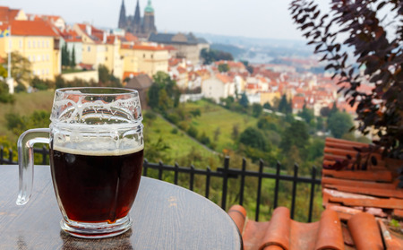 Czech Republic. Prague. Glass of beer on the table terrace Petrin hill. View of Prague Castle.