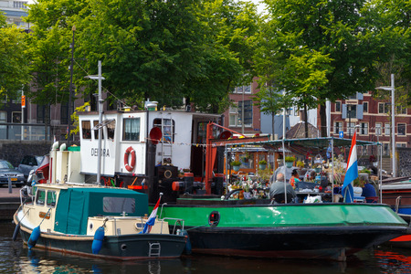 Amsterdam, Netherlands - July 31, 2014: Traditional house boat on the canals of Amsterdam. In Amsterdam, there are about 2,500 homes on the water.