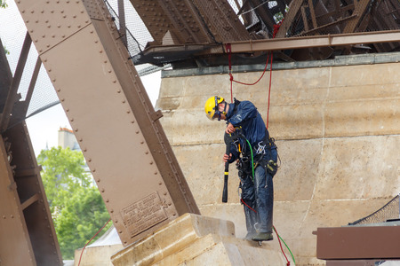 steeplejack: Paris, France - May 9, 2014: Man steeplejack washes foundation of the Eiffel Tower.
