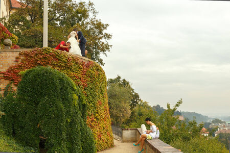 Prague, Czech Republic - September 30, 2014: Newlywed couple relaxing on the parapet at Prague Castle.
