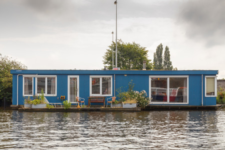 Amsterdam, Netherlands - July 29, 2014: Traditional house boat on the canals of Amsterdam. In Amsterdam, there are about 2,500 homes on the water. Editöryel