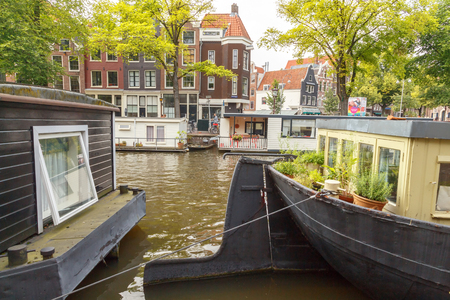 typically dutch: Amsterdam, Netherlands - July 29, 2014: Canals of Amsterdam. Favorite place for walking and leisure travelers.