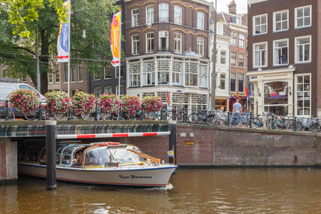 typically dutch: Amsterdam, Netherlands - July 30, 2014: Canals of Amsterdam. Favorite place for walking and leisure travelers. Editorial