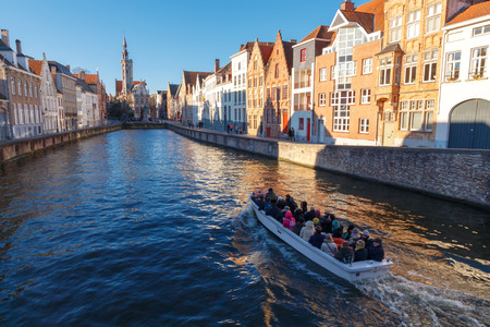 flemish: Bruges, Belgium - December 28, 2014: Excursion tour by boat on the canal Spiegel Rei of the medieval city of Bruges, Belgium.