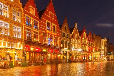 bruges: Bruges, Belgium - December 23, 2014: Central Bruges Market Square at sunset decorated at Christmas.