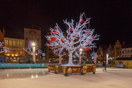 bruges: Bruges, Belgium - December 24, 2014: Central Bruges Market Square decorated at Christmas. A man pours water at night skating rink.