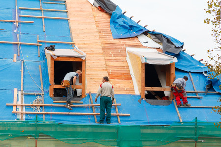 house robe: Prague, Czech Republic - October 1, 2014: Men roofers on the roof make waterproofing and put tile.