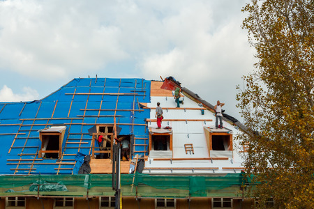 waterproofing: Prague, Czech Republic - October 2, 2014: Men roofers on the roof make waterproofing and put tile.