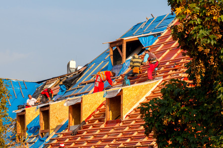 house robes: Prague, Czech Republic - October 6, 2014: Men roofers on the roof make waterproofing and put tile. Editorial