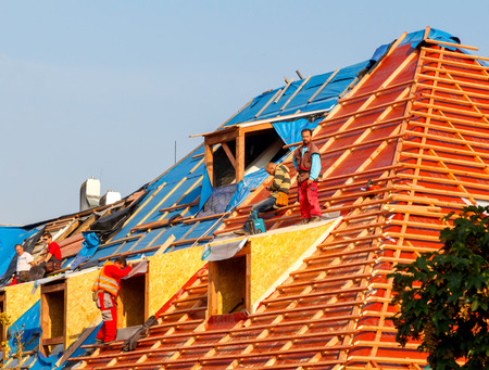 waterproofing: Prague, Czech Republic - October 6, 2014: Men roofers on the roof make waterproofing and put tile. Editorial