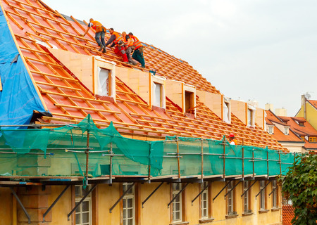 roof ridge: Prague, Czech Republic - October 30, 2014: Men roofers on the roof make waterproofing and put tile.