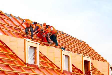 house robes: Prague, Czech Republic - October 30, 2014: Men roofers on the roof make waterproofing and put tile.