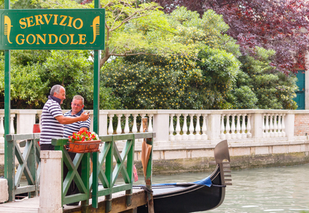gondoliers: Venice Italy May 20 2015: Two men relaxing on the dock gondoliers parking gondola. Gondoliers in Venice separate prestigious profession employs about 400 people. Editorial