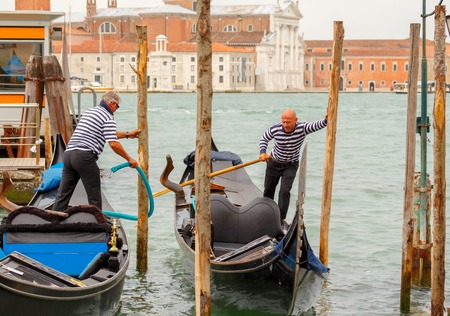 gondoliers: Venice Italy May 20 2015: Two men gondoliers moor their gondola in piles. Gondoliers in Venice separate prestigious profession of about 400 people.