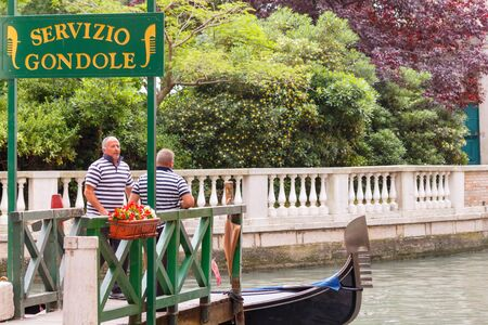 prestigious: Venice Italy May 20 2015: Two men relaxing on the dock gondoliers parking gondola. Gondoliers in Venice separate prestigious profession employs about 400 people. Editorial