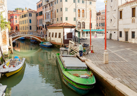 specificity: Venice Italy May 24 2015: Men cleaners engaged in loading trash in a special barge morning in Venice. Removal garbage in Venice is only possible on the water. Editorial