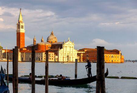 paisaje mediterraneo: Hermosa vista de las Laguna de Venecia de la isla con la iglesia de San Giorgio Maggiore y la góndola al atardecer. El montar en una góndola es uno de los espectáculos más populares de los turistas en Venecia. Foto de archivo