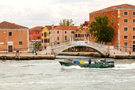 gondoliers: Venice Italy May 21 2015: Cargo Venetian motor barge. All products and goods delivered to Venice by sea and canals in the city.
