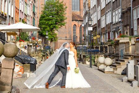 honeymooners: Gdansk, Polonia - 28 de julio de 2015: Una pareja en el vestido de novia es fotografiado en la calle Mariacka de Gdansk. Vieja calle medieval es muy popular entre los reci�n casados ??y turistas.