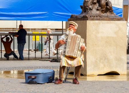 musico: Varsovia, Polonia - 25 de julio de, 2015: El viejo entretiene a los turistas que juegan el acordeón en la plaza del mercado de Varsovia. Músicos de la calle uno de los atractivos de Varsovia. Editorial