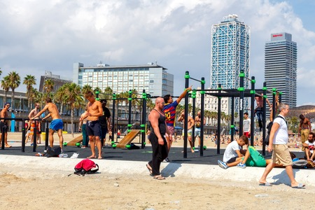 play popular: Barcelona, Spain - September 5, 2015: Barceloneta is one of the most popular city beaches of Barcelona. Many tourists come here to sunbathe, swim and play sports.