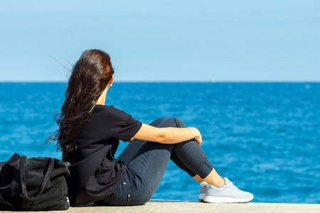 Young girl sitting on the edge of the pier and watching the blue sea. Stok Fotoğraf