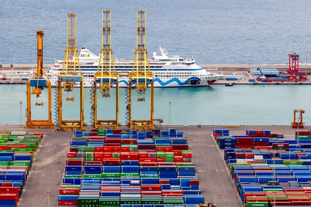 mass storage: Barcelona, Spain - September 4, 2015: View of the cargo port and container terminal of Barcelona with the Montjuic hill.