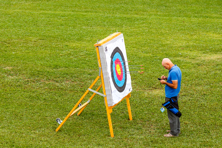 active arrow: Barcelona, Spain - September 4, 2015: Archer Man in front of a target. Archery is a popular sport in Europe.