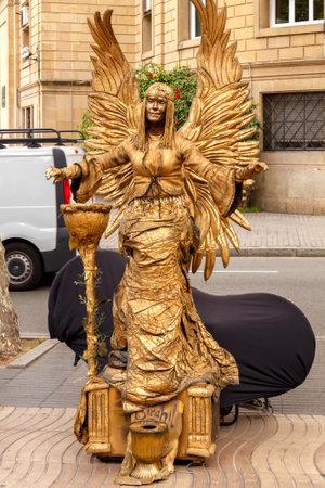 rambla: Barcelona, Spain - September 4, 2015: Live statue of angel on La Rambla. A popular attraction for tourists.