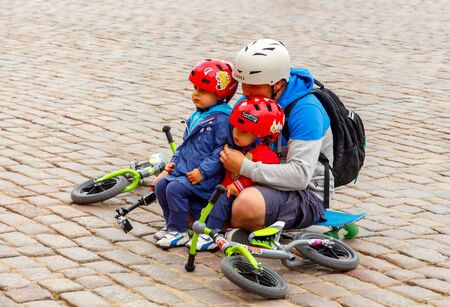 people in action: Warsaw, Poland - July 26, 2015: Dad with two children wearing helmets with bicycles resting on the castle square.