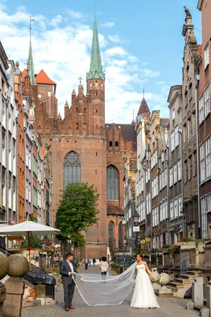 honeymooners: Gdansk, Poland - July 28, 2015: A couple in the wedding dress is photographed on the Mariacka streets of Gdansk . Old medieval street is very popular among honeymooners and tourists.