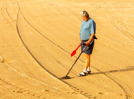 magnetic field: Tossa de Mar, Spain - September 12, 2015: Man looking for lost jewelry with metal detector on the beach of Tossa de Mar. Famous tourist resort on the Mediterranean coast. Editorial
