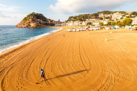 metal detector: Tossa de Mar, Spain - September 12, 2015: Man looking for lost jewelry with metal detector on the beach of Tossa de Mar. Famous tourist resort on the Mediterranean coast. Editorial
