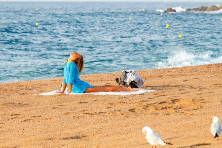 lore: Lloret de Mar, Spain - September 13 2015: Young girl doing gymnastics on the beach in Lloret de Mar in the early morning. Lore de Mar is one of the best resorts in Spain.
