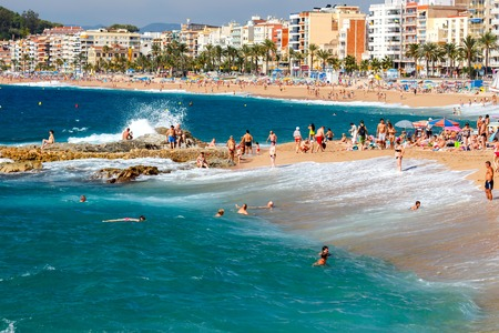 fun day: Lloret de Mar, Spain - September 13 2015: A crowd of vacationers enjoy the warm beaches of the Costa Brava in Lloret de Mar. Lloret de Mar is one of the largest resorts on the coast of Spain.