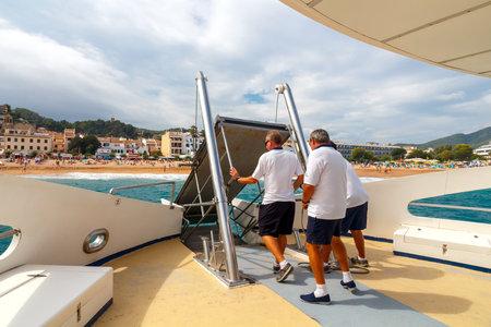 disembark: Tossa de Mar, Spain - September 13, 2015: Passengers disembark from a boat on the beach at Tossa de Mar. Along the Costa Brava conducted intensive passenger traffic.