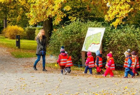 kinder: Tallinn, Estonia - 19 de octubre 2015: Una maestra de preescolar con ni�os peque�os vestidos con chalecos reflectantes de seguridad para un paseo por el parque en Tallin.